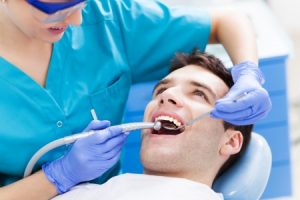 man having teeth examined by dentist